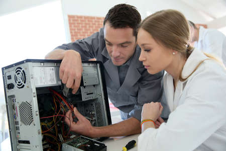 computer repairing: Teacher with student in technology repairing computer Stock Photo