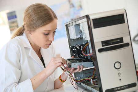 redes electricas: Muchacha del estudiante en la tecnología fixug disco duro del ordenador Foto de archivo