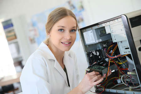 computer repairing: Student girl in technology fixug computer hard drive Stock Photo