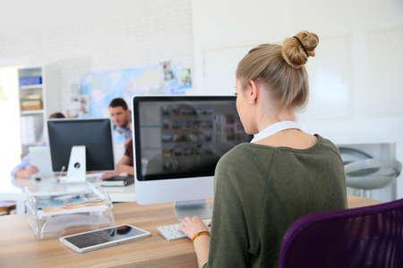 trabajando en computadora: Muchacha del estudiante que trabaja en el ordenador de escritorio