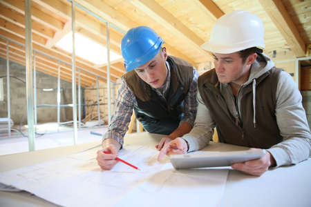 young men: Young men in professional training working on building site