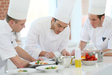Chef training students in restaurant kitchen Фото со стока