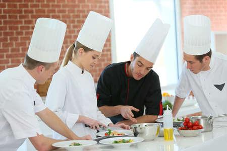Chef training students in restaurant kitchen Foto de archivo