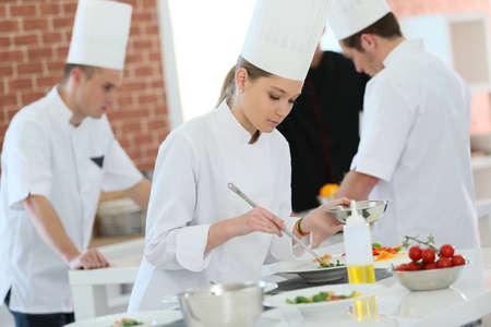 students in class: Girl in cooking training class preparing dish Stock Photo