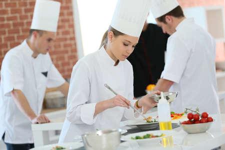 Girl in cooking training class preparing dish Archivio Fotografico