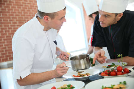 culinary: Chef with young cook in kitchen preparing dish Stock Photo