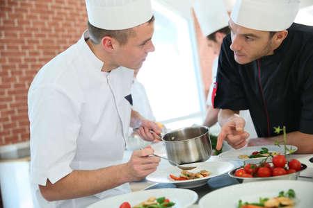 Szef kuchni z młodego kucharza w kuchni przygotowując potrawy Zdjęcie Seryjne