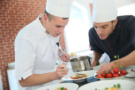cook: Chef with young cook in kitchen preparing dish Stock Photo