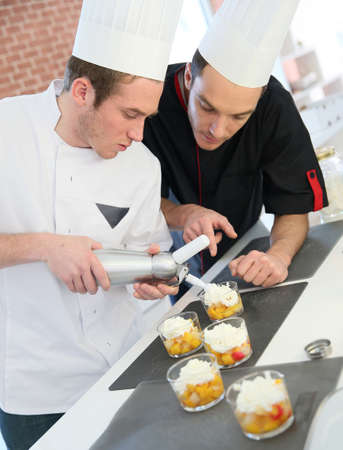siphon: Young cook preparing dessert with chef behind him Stock Photo
