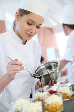 postres: Pasteler�a cook estudiante verter la salsa de chocolate de postre