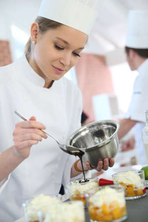 Pastry cook student pouring chocolate sauce on dessert Stock Photo - 37490870