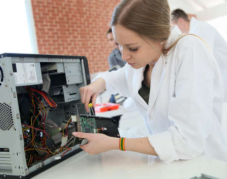 inside technology: Student girl in technology fixing computer hard drive Stock Photo