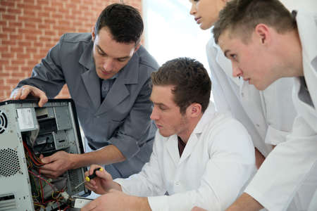 Students in computing class with teacher fixing hardware photo
