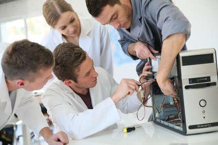 electricista: Los estudiantes en la clase de computaci�n con las piezas de fijaci�n maestro