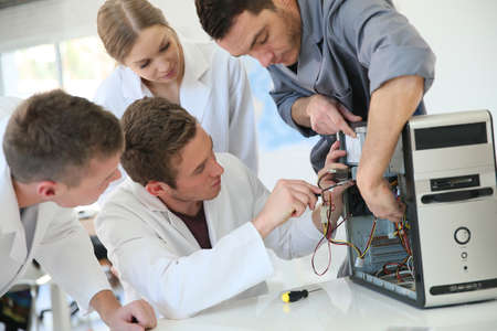 repair computer: Students in computing class with teacher fixing hardware Stock Photo