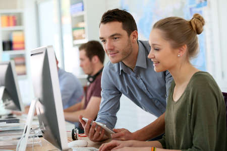 curso de capacitacion: Muchacha del estudiante con el entrenador trabaja en el ordenador y la tableta