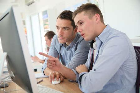 maestro: Profesor con el estudiante que trabaja en el escritorio