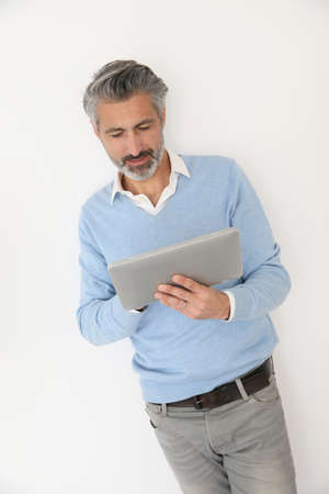 websurfing: Handsome mature man websurfing with tablet, isolated Stock Photo