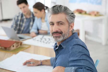 Portrait of smiling teacher in architecture