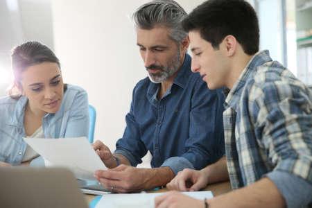 maestra ense�ando: Estudiantes con entrenador trabajando en el proyecto