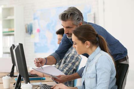 curso de capacitacion: Entrenador con estudiante que trabaja en la computadora de escritorio
