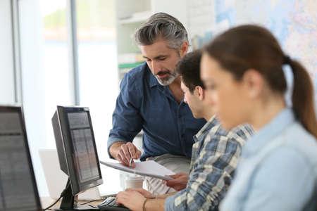 Leraar met jonge mensen in de informatica klasse