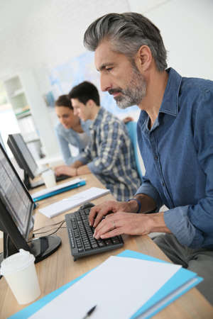 computer classes: Smiling teacher working on desktop computer