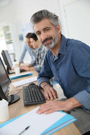 desktop computer: Smiling teacher working on desktop computer