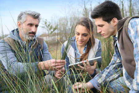 Working Environment: Teacher with students in agronomy looking at vegetation Stock Photo
