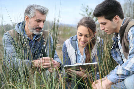 Teacher with students in agronomy looking at vegetation Banque d'images