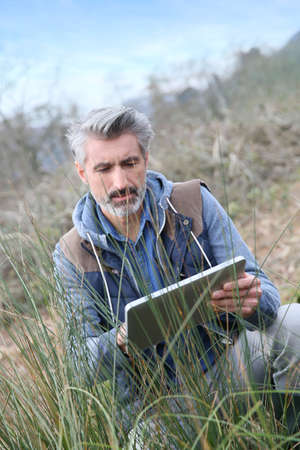 agronomist: Agronomist using tablet and checking on vegetation