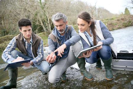 Water pollution: Nhà sinh vật học với các sinh viên trong nước sông thử nghiệm khoa học