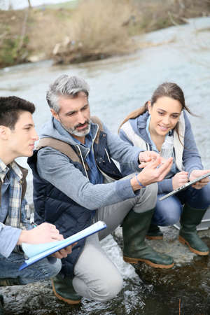 biologist: Biologist with students in science testing river water Stock Photo