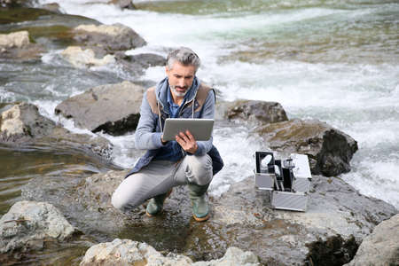 water quality: Biologist testing quality of natural water Stock Photo