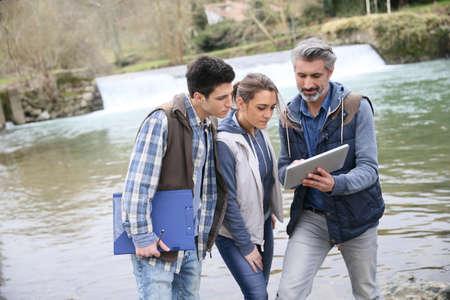 metodo cientifico: Porfessional con los estudiantes en la biología de pie por el río Foto de archivo