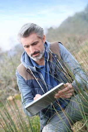 Agronomist using tablet and checking on vegetation