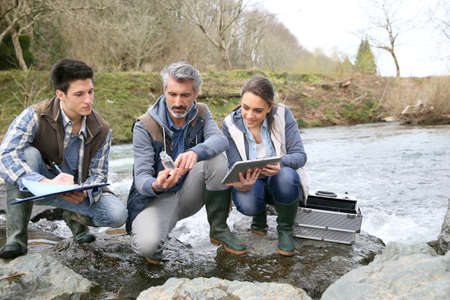Biologist with students in science testing river water photo