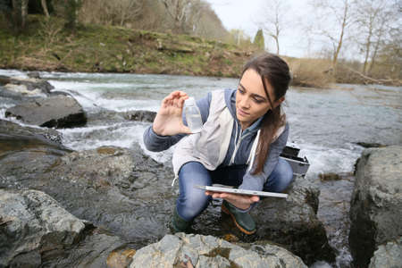 Student in biology taking sample of natural water