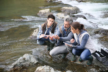 polluted river: Biologist with students in science testing river water Stock Photo