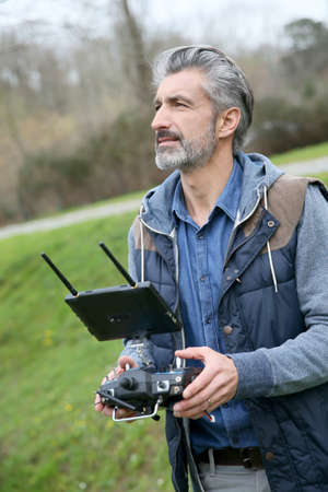 drone: Man operating a drone with remote control Stock Photo