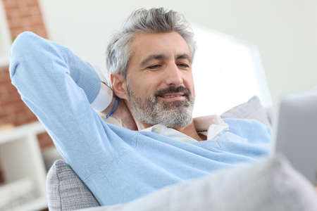 websurfing: Mature handsome man websurfing on tablet at home Stock Photo