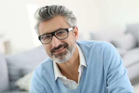 Smiling mature man with grey hair wearing eyeglasses