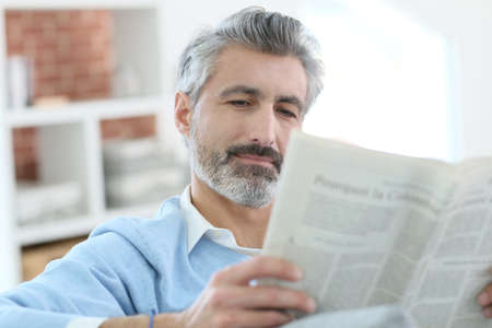 Mature man reading newspaper sitting in sofa Banque d'images