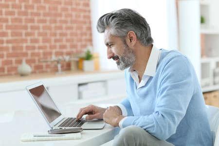 ノート パソコンで自宅で仕事をトレンディな成熟した男
