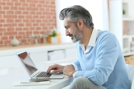 Trendy mature man working from home with laptop Stockfoto