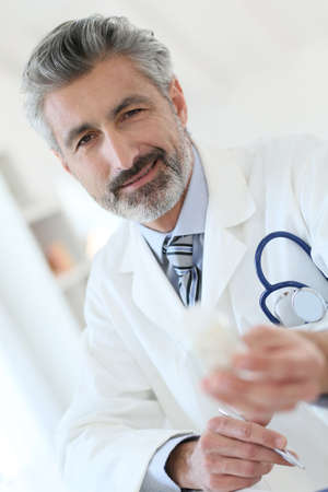 medicalcare: Mature doctor in hospital giving pills to patient
