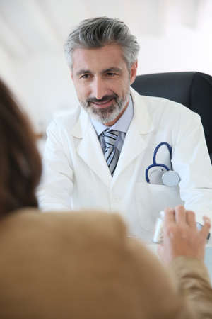 medicalcare: Doctor giving prescription to patient Stock Photo