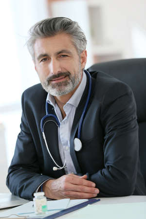 Portrait of mature doctor in office photo