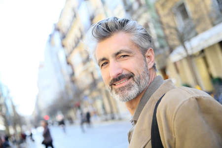 handsome old man: Handsome mature man walking in town Stock Photo