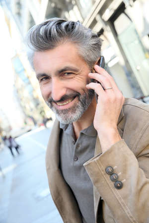 Mature man talking on the phone in the street photo